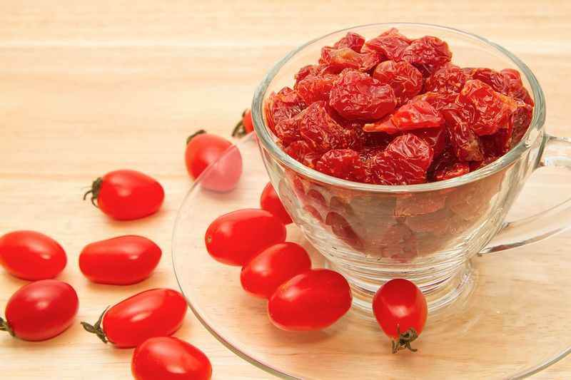 Dried tomatoes in glass on wooden background